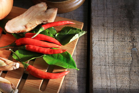 Close up chili and galangal and lemon grass and ginger on the wood table in thai kitchen with sunlight from the window Stock Photo