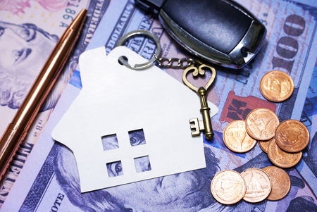 House s key and pen and coin and car s key on background dollar banknote, investment concept.