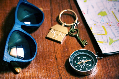 Compass and sunglass and key and tourist map on wood table. Stock Photo