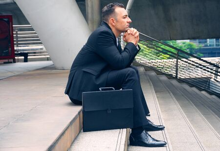 Businessman sit alone on the stairs and feel stressed by layoff from work