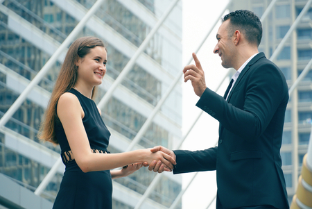 Business woman shaking hands with client after successful negotiation trade agreement.