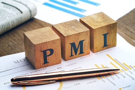 Text PMI on wood cube and gold pen lay on chart candle document paper , economic data concept.