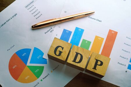 """Text """"GDP"""" on wood cube decorate with pen lay on document pie and candle chart data, economic data concept. Imagens"""