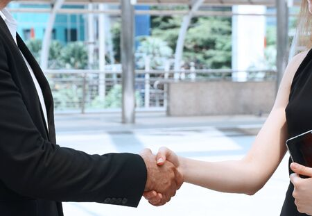 Man shaking hands with client women after talking business