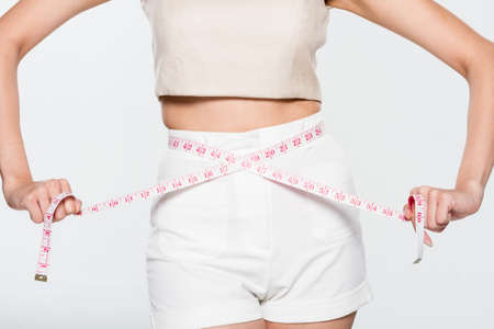 Woman measuring her waistline on isolated background