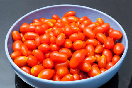 Group of Fresh Rape Cherry Tomatoes in Blue Bowl
