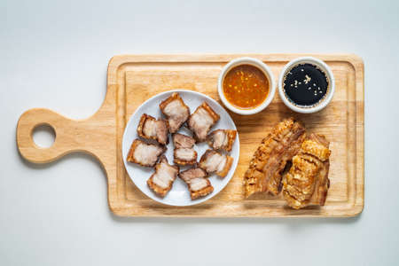 Deep Fried Crispy Streaky Pork Belly Thai and Chinese Food on Cutting Board with Sauce and Ginger on Isolated Background.