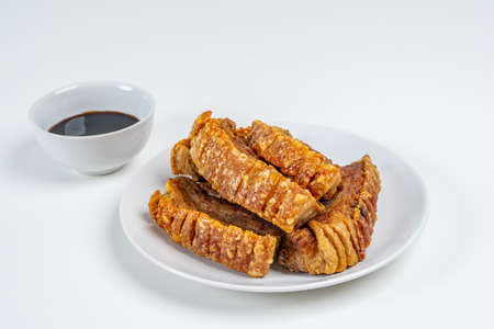 Deep Fried Crispy Streaky Pork Belly Thai and Chinese Food on White Plate with Sauce and Ginger on Isolated Background.