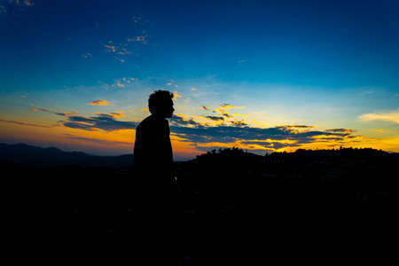Silhouette Happy Man Standing on Hill at the Sunset on Mountain with Blue  Sky. Enjoying Peaceful Moment Concept.Relaxing or achievement Concept.