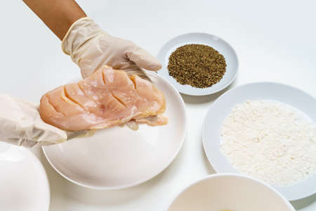 Close Up Chef's Hand with Raw Chicken Breast Fillets for Cooking with Flour, Eggs, Herbs and Peppers on White Table.