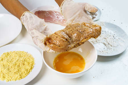 Close Up Chef's Hand with Raw Chicken Breast Fillets Cooking Drop into Eggs Yolk with Flour, Eggs, Herbs and Peppers on White Table.