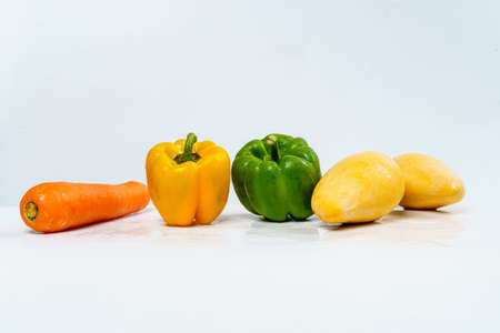 Mix Fruits for Healthy Eating, Carrot, Bell Pepper and Mangos with Water Drop on Isolated White Background.
