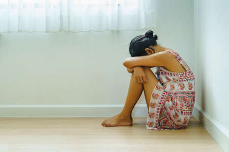 Depressed of Young Asian Woman Sitting Alone and Hugging her Knees at the Corner in the House. Desperate, Depressive Disorder, or Sadness Concept.
