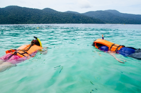 couple snorkeling in sea photo