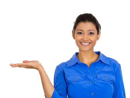 Closeup portrait of happy pretty confident young smiling woman gesturing to space at left with palm up