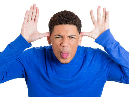 ridiculous: Closeup portrait of funny angry young childish rude bully man sticking his tongue out at you camera gesture, isolated on white background  Negative emotions facial expression feelings  Signs, symbols