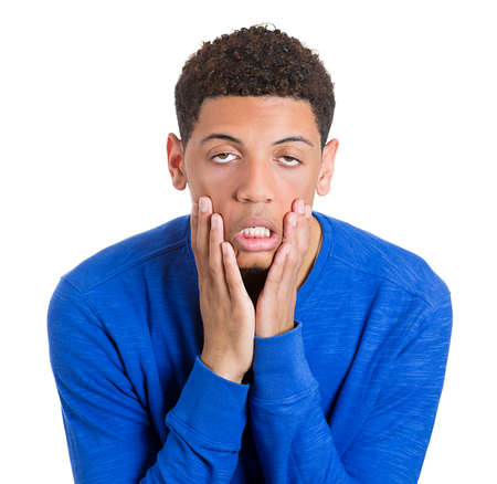 Closeup portrait of overwhelmed tired young man dragging cheeks down with hands, isolated on white background. Negative emotion facial expression feelings, attitude, body language Stock Photo