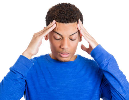 Closeup portrait of worried young man having really bad headache hurt pain placing both hands on temples, isolated on white background. Negative emotion facial expressions feelings, body language photo