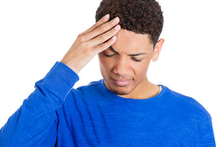 Closeup portrait of worried young man having really bad headache hurt pain placing hand on forehead, isolated on white background. Negative emotion facial expressions feelings, body language photo