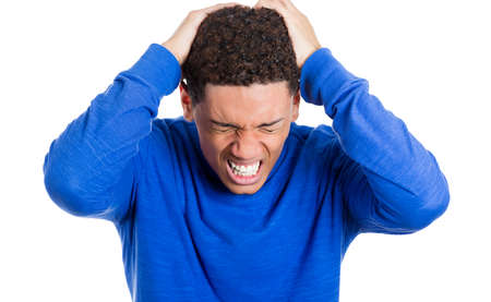 Closeup portrait of worried young man having really bad headache hurt pain placing both hands on back of head, isolated on white background. Negative emotion facial expressions feelings, body language photo