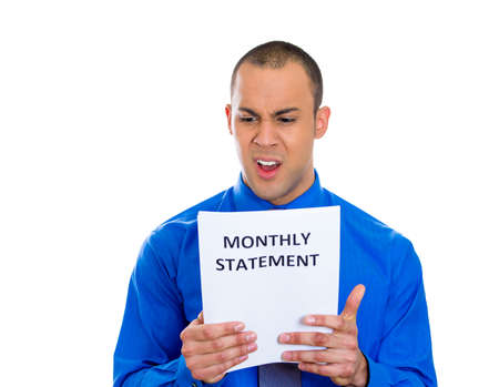 bank records: Closeup portrait of pissed off young man looking shocked and disgusted at his monthly statement, isolated on white background. Negative emotion facial expression feelings. Financial crisis, bad news Stock Photo
