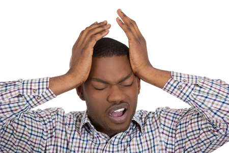 Closeup portrait of worried young man having really bad headache hurt pain placing both hands on temples, isolated on white background. Negative human emotion facial expressions feelings photo