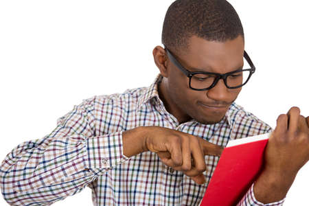 Closeup portrait of young man, squinting eyes pointing at a page inside book, upset annoyed by the twists and turn of story, isolated on white background. Human emotion facial expression Stock Photo