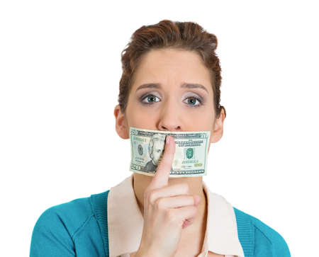 under paid: Closeup portrait of silent corrupt woman with twenty dollar bill taped to mouth and showing shhh sign, isolated on white background. Bribery concept in politics, business, and diplomacy.