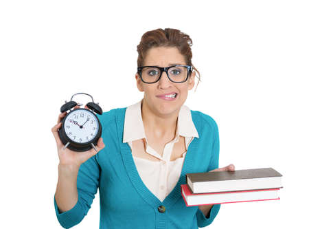 Closeup portrait of nerdy young woman with glasses carrying tons of books, stressed from project deadline, isolated on white background. Negative emotion facial expression feelings, body language photo