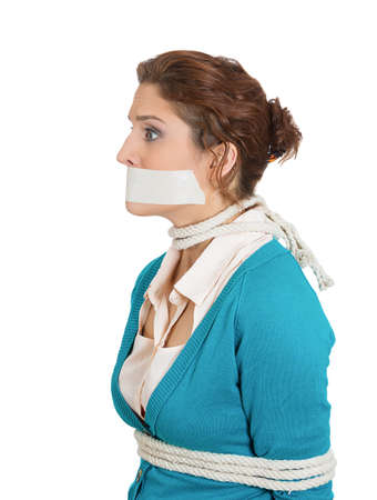 misdemeanor: Closeup portrait of uncomfortable concerned scared woman with mouth taped shut and tied with rope, kidnapped, isolated on white background.  Social injustice, human depravity, misdemeanor, felony.