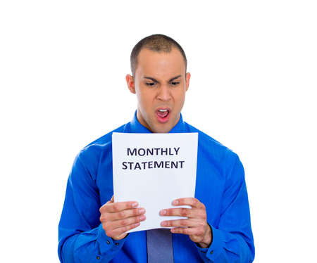 bank records: Closeup portrait of pissed off young man looking shocked and disgusted at his monthly statement, isolated on white background  Negative emotion facial expression feelings  Financial crisis, bad news