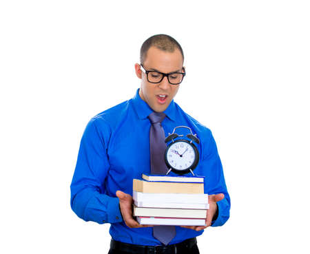 lack of confidence: Closeup of a young nerdy man, wearing big black glasses, holding books and clock, anxious in anticipation of finals exam test, isolated on white background  Negative facial expression feeling emotions