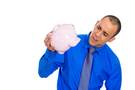 bad economy: Closeup portrait of poor stressed, upset, sad, unhappy young adult man holding empty piggy bank, debt, isolated against white background  Financial difficulties, bad economy concept  Negative emotion