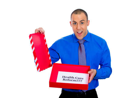 Closeup portrait of young super excited happy man holding gift with health care reform sign inside, isolated on white background  Universal health care coverage, politics, government, legislation photo
