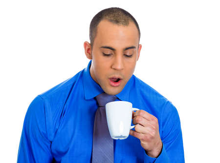 eyes opened: Closeup portrait of very tired falling asleep young man holding cup of coffee struggling not to crash and stay awake, keeping his eyes opened, isolated on a white background  Negative emotion feelings