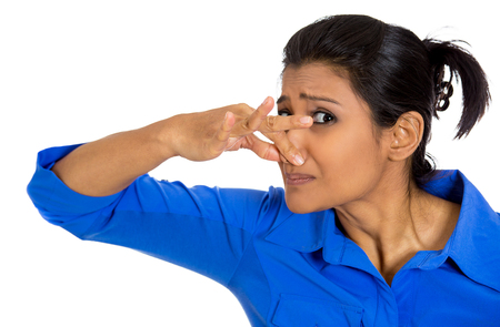 stinks: Closeup portrait of pretty young woman closing covering nose, something stinks, isolated on white background. Negative facial expressions, emotions, feelings, reaction, attitude, behavior, perception