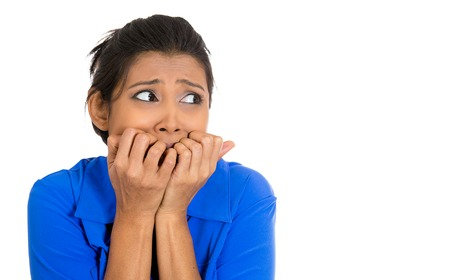 Closeup portrait of young unhappy woman biting her nails and looking at you with a craving for something or anxious worried isolated on white background. Negative emotion facial expression feelings photo