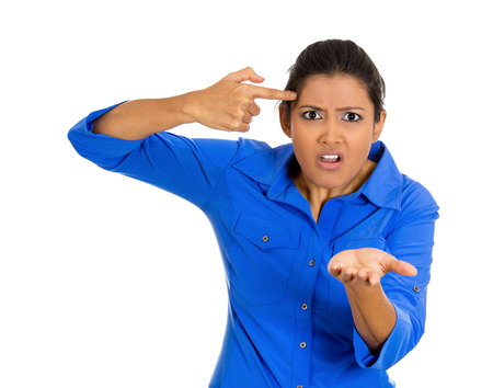 unprofessional: Closeup portrait of an angry pretty young woman gesturing with her finger against temple asking are you crazy? Isolated on white background. Negative emotions facial expression feelings, body language Stock Photo