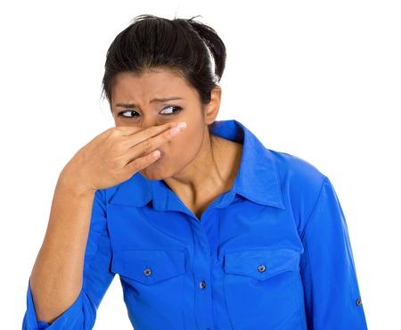 Close-up portret van mooie jonge vrouw afsluiting die neus, iets stinkt, geïsoleerd op een witte achtergrond. Negatieve gezichtsuitdrukkingen, emoties, gevoelens, reactie, houding, gedrag, perceptie Stockfoto