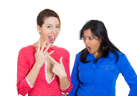 covetous: Closeup portrait of woman super excited to be engaged pointing to ring, and other lady looking very envious at her friend good fortune, isolated on white background. Negative emotion facial expression