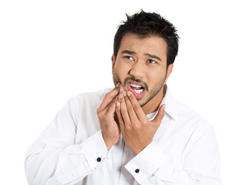 Closeup portrait young man with sensitive toothache bridge problem about to cry from oral pain touching outside mouth with hand, isolated white background. Negative emotion facial expression feeling photo
