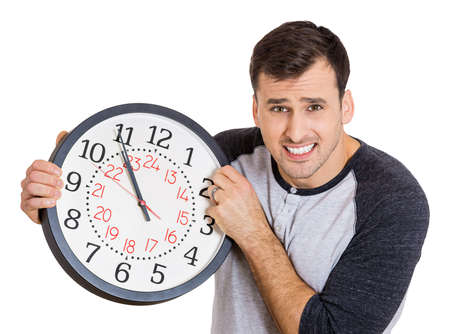 pressured: Closeup portrait of  business man, student, worker holding clock looking anxiously, pressured by lack of time, running out of time, isolated on a white background. Human face expressions, emotions