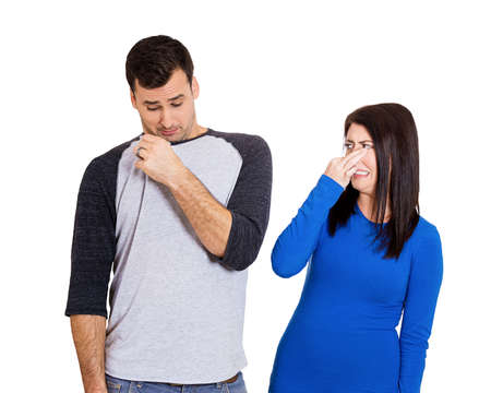 Closeup portrait of woman looking at man closing, covering nose, something stinks, very bad smell, odor. Guy sniffs himself. Isolated on white background. Negative emotion, facial expression, feeling