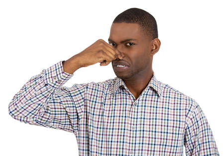 stinks: Closeup portrait of young man, disgust on his face, pinches his nose looks at you, something stinks, very bad smell, situation, isolated on white background. Negative emotion facial expression feeling