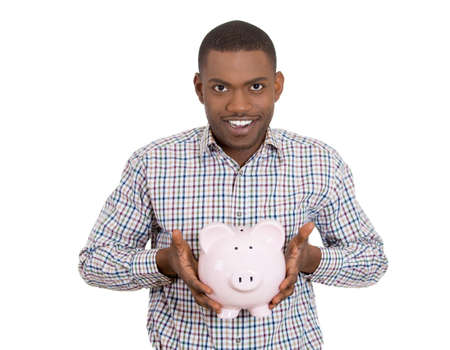 Closeup portrait of smiling man, student, young guy, worker holding piggy bank, happy about his savings, isolated on white background. Smart financial investment decisions. Budget management, control photo