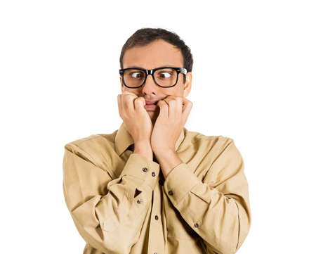 Closeup portrait of a nerdy guy, anxious man with big glasses, biting his finger nails craving something scared, eyes crossed isolated on white background. Negative human emotions, facial expressions