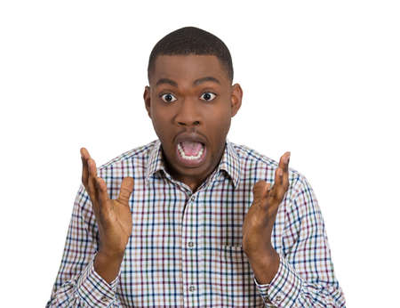 wtf: Closeup portrait of handsome young man hands up wide open mouth and eyes stunned dumbstruck dumbfounded looking at camera gesture, isolated on white background. Human emotions facial expression
