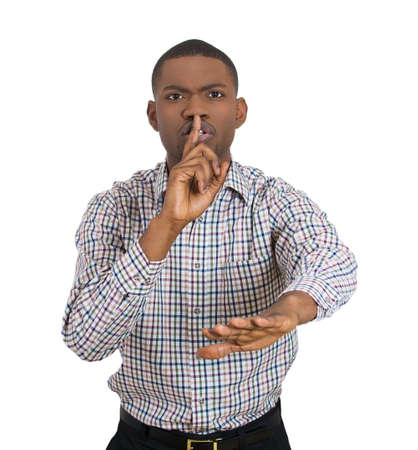 hushed: Closeup portrait of young man placing finger on lips to say, shhhhh, be quiet, gesture with hand isolated on white background. Negative facial expression feelings, human emotions signs and symbols