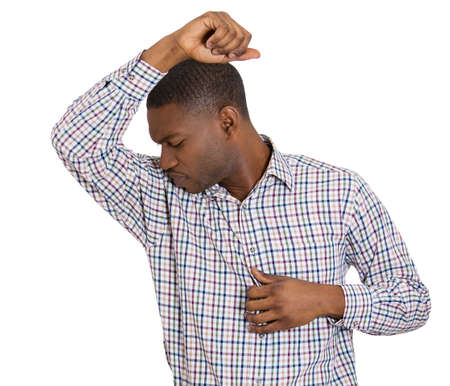 stinks: Closeup portrait of young man, smelling, sniffing his armpit, something stinks, very bad smell, odor. Guy sniffs himself. Isolated on white background Negative emotion, facial expression, feeling
