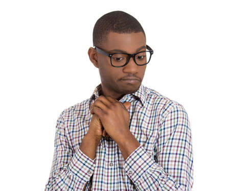 goon: Closeup portrait of a young nerdy looking man with glasses, very timid, suspicious shy and anxious looking away down isolated on white background. Mental health, emotion facial expression feeling Stock Photo